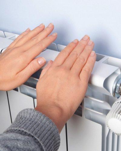 Personne se réchauffant les mains sur un radiateur